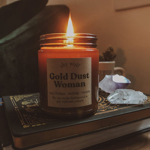Shy Wolf Gold Dust Woman candle on a live edge wood nightstand with tarot books.