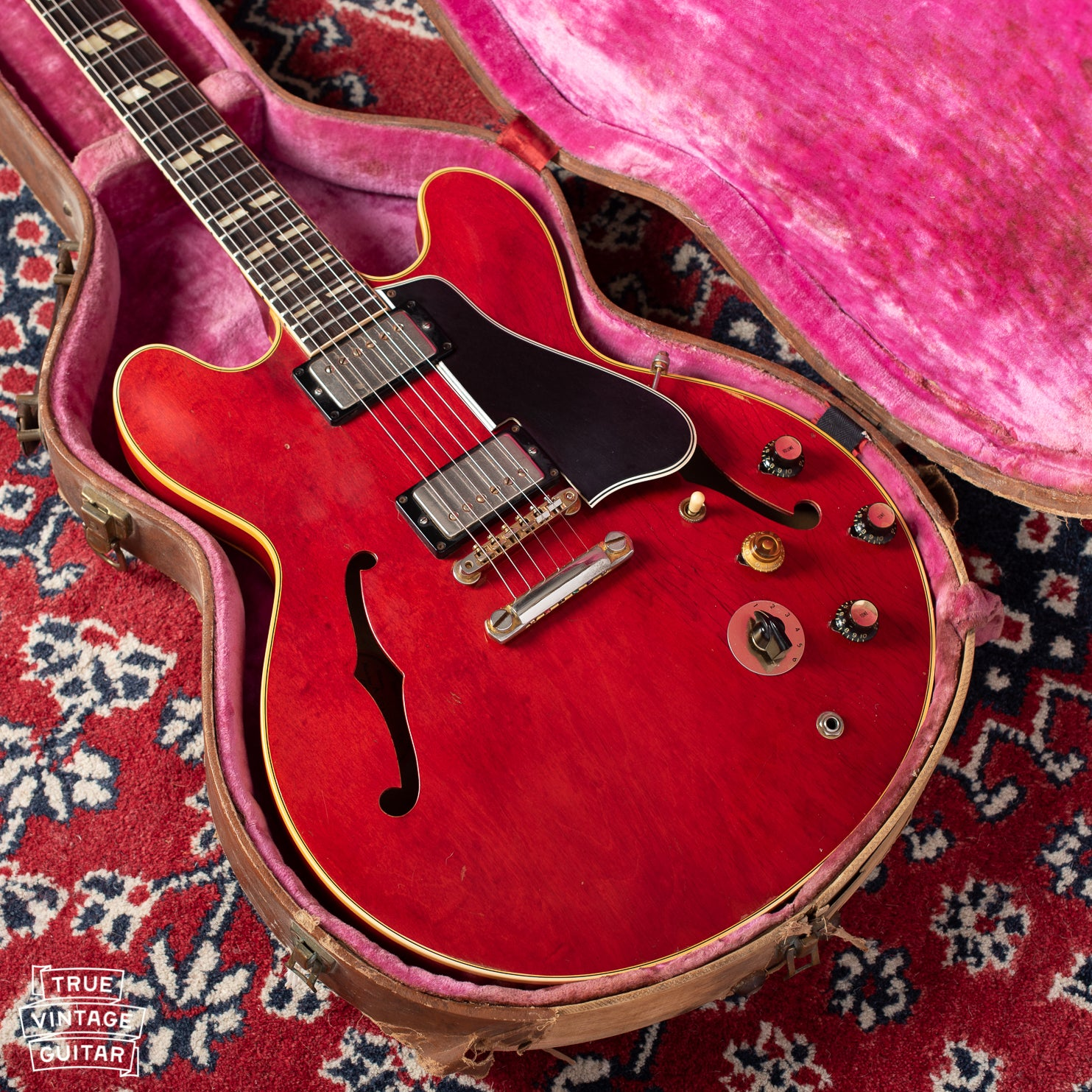 Gibson ES-345 guitar red with stop bar stop tail tailpiece and long pickguard. Pink interior case with brown exterior Lifton.