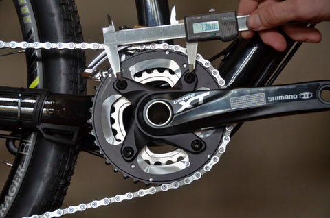 A caliper measuring the distance between two adjacent bolts on a chainring on a bicycle