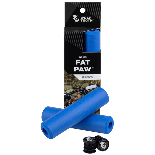 Wolf Tooth Fat Paw handlebar grips in blue both in packaging and sitting in front of packaging with bar end plugs