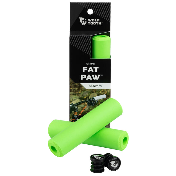 Wolf Tooth Fat Paw handlebar grips in green both in packaging and sitting in front of packaging with bar end plugs