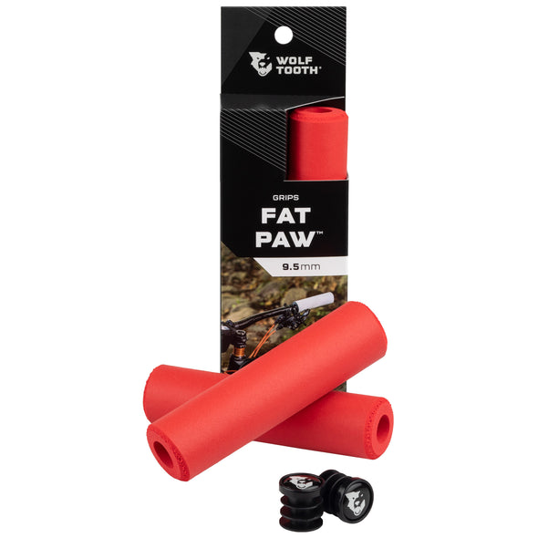 Wolf Tooth Fat Paw handlebar grips in red both in packaging and sitting in front of packaging with bar end plugs