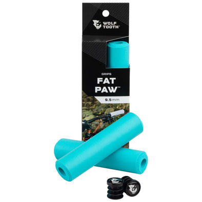 Wolf Tooth Fat Paw handlebar grips in teal both in packaging and sitting in front of packaging with bar end plugs