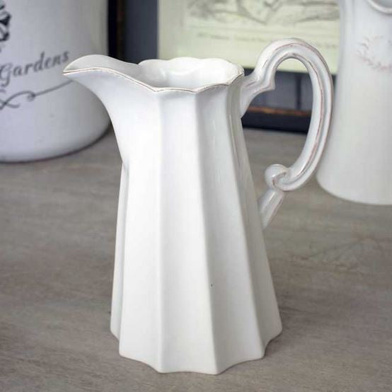 White ceramic pitcher with scalloped edge