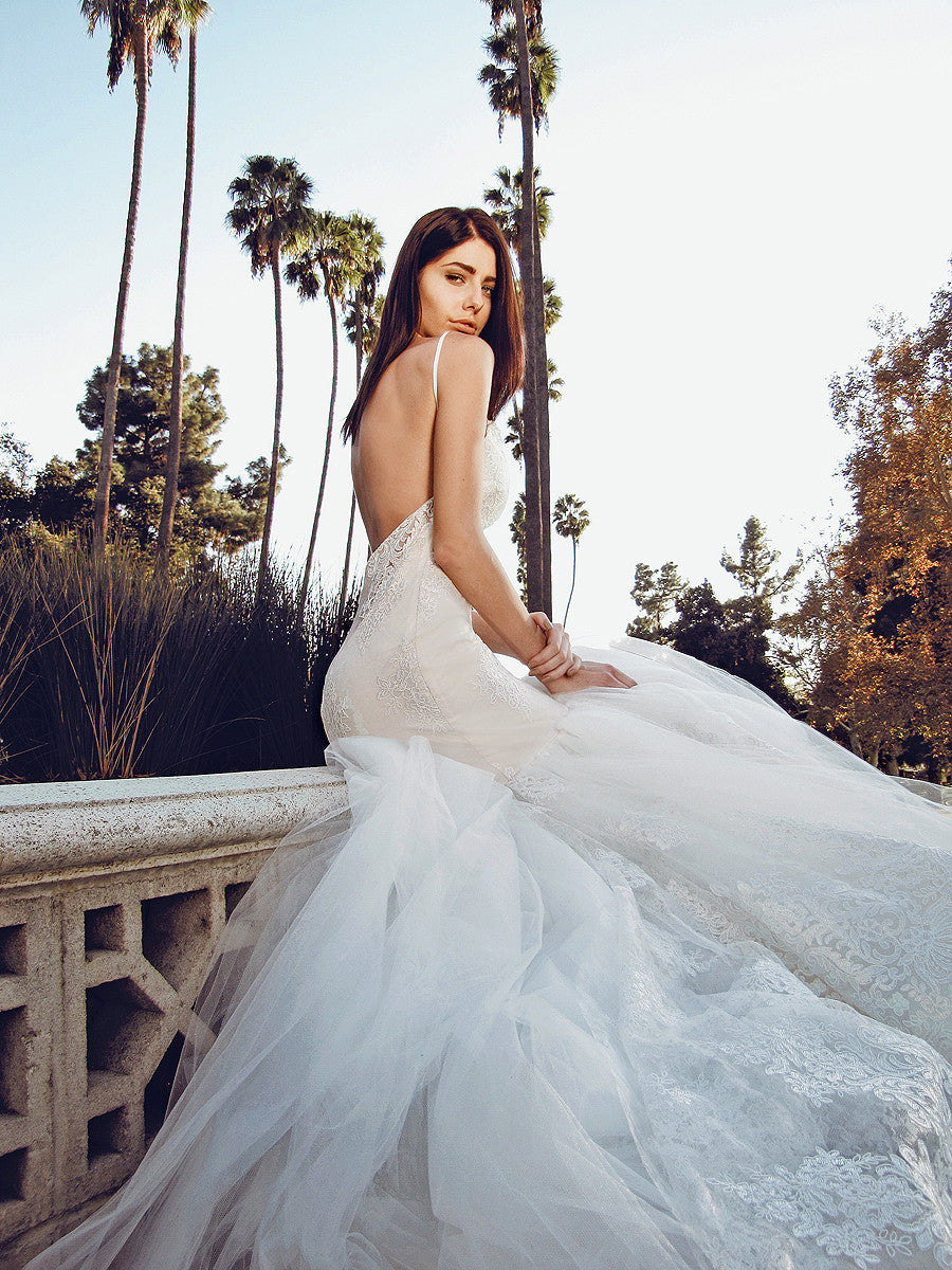Dramatic and sexy backless mermaid wedding gown with cathedral tulle and scalloped lace train pictured in park