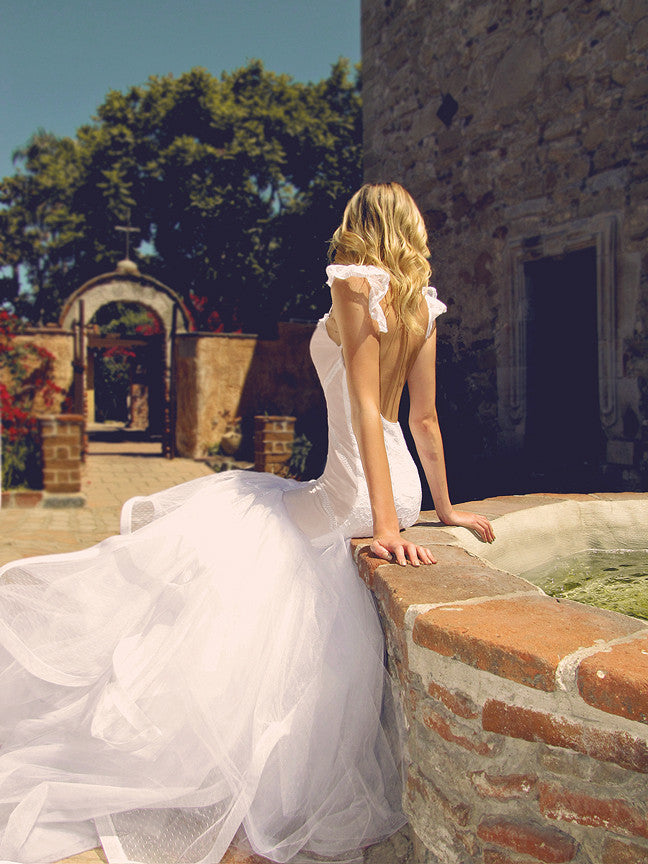 Backless mermaid wedding gown with lace sleeves.