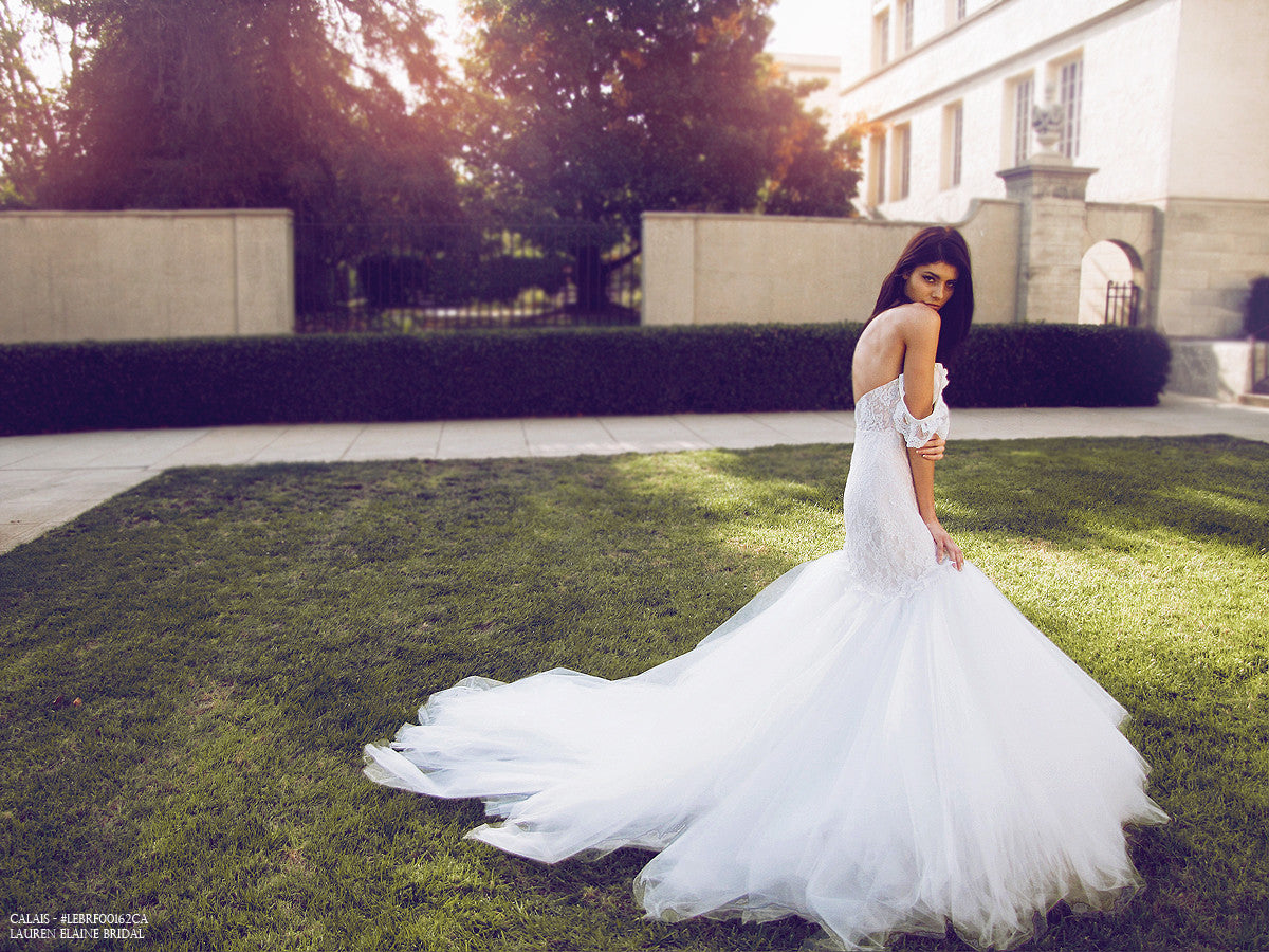 Dramatic mermaid wedding gown with cathedral train and off-the-shoulder lace sleeves.