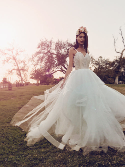 Fairytale blush tulle and lace ball gown wedding dress with horsehair hem twirling in the sunset.
