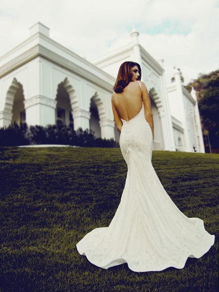 Backless lace wedding gown with satin-covered buttons. Open back bridal gowns