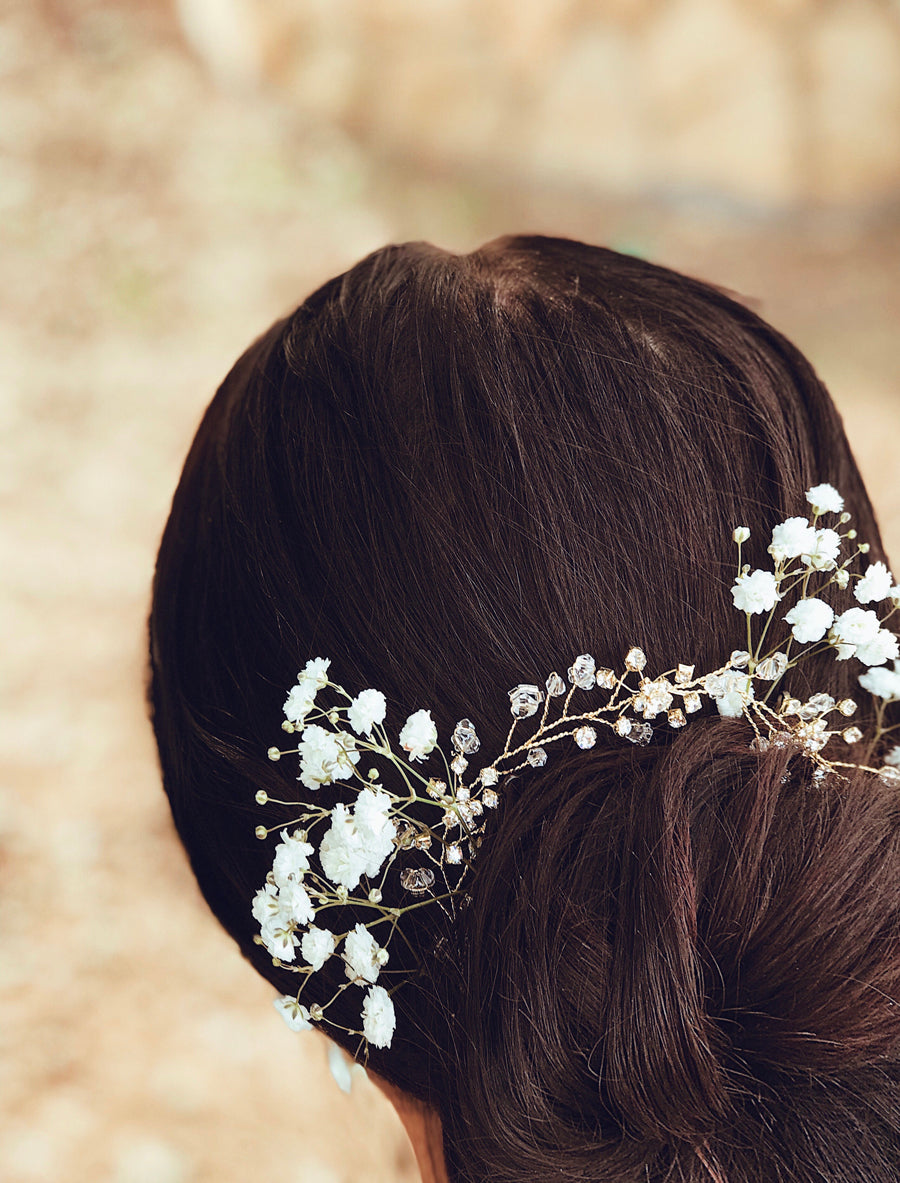 "A bride wears the ""Laurel"" flower crown and hair vine from Lauren Elaine Bridal Accessories paired with baby's breath flowers"