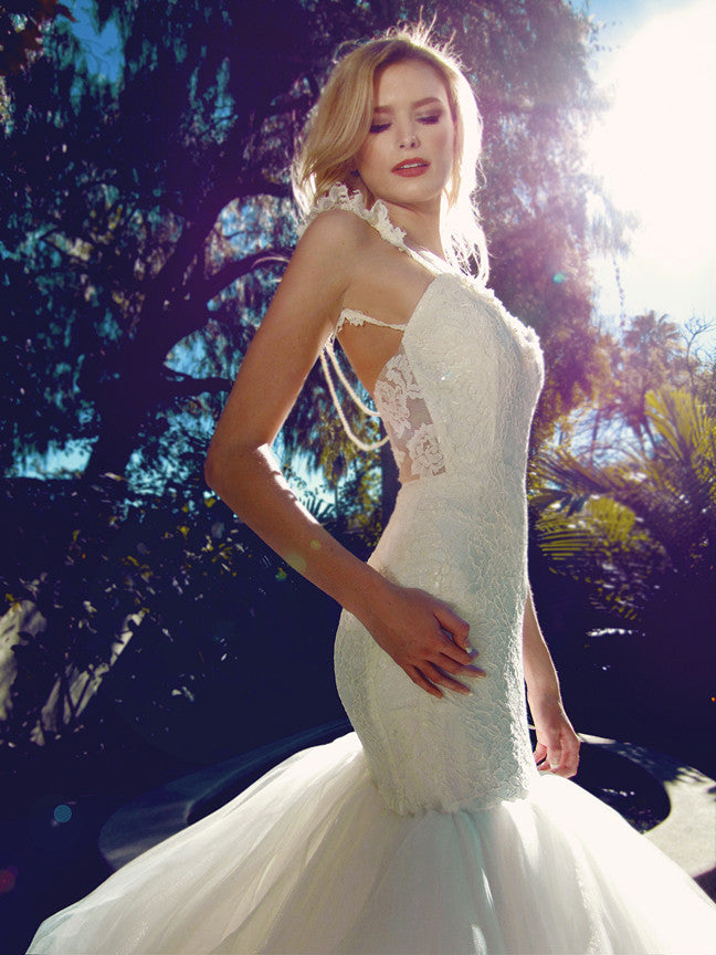 Backless mermaid wedding gown with pearl detailing and lace appliques.
