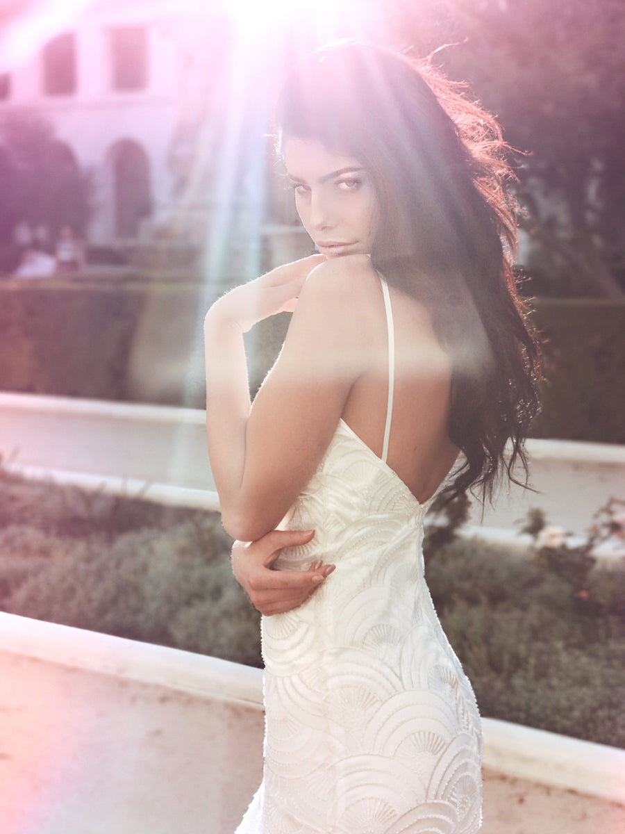Sexy beaded sheath wedding dress with satin spaghetti straps and low back.