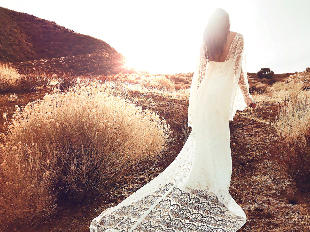 Ethereal and bohemian lace sheath wedding dress with cape sleeves from Lauren Elaine Bridal.