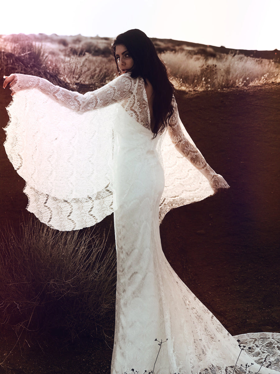 Bohemian beach and destination wedding dress with festival inspired cape sleeves.
