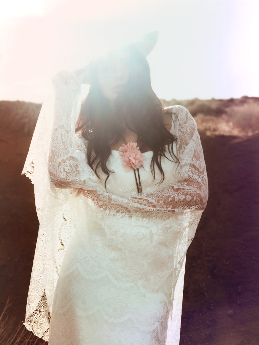 Cowgirl and western inspired bohemian wedding dress with angel wing cape sleeves.
