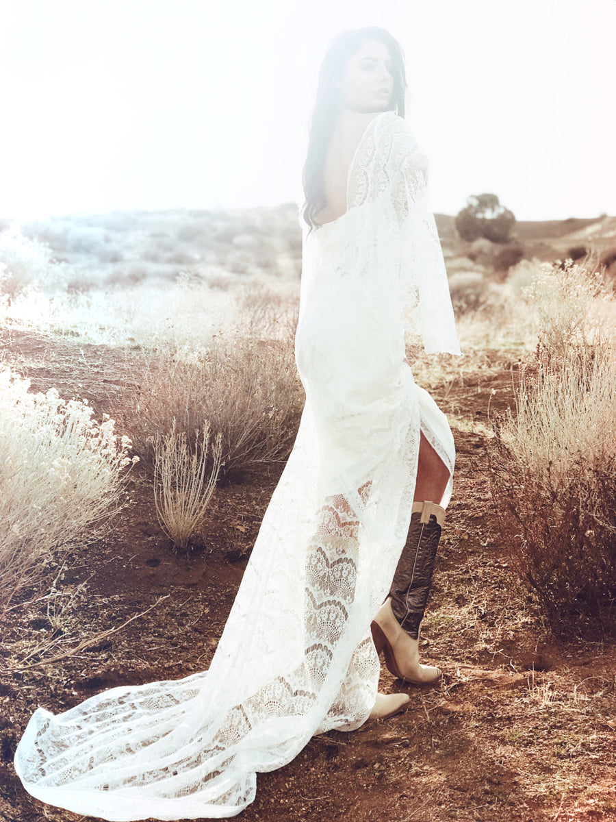 Vintage feel bohemian sheath wedding dress with lace cape sleeves.