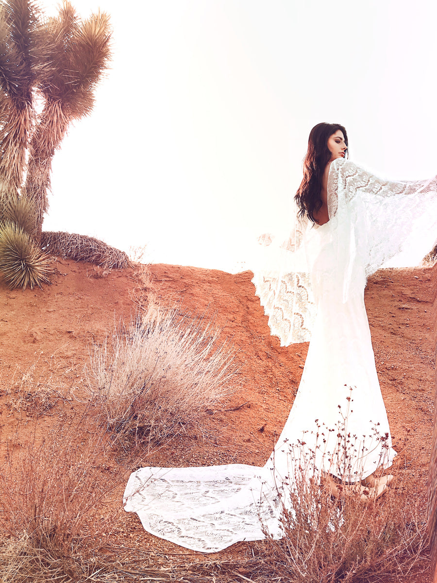 Bohemian lace sheath wedding gown with angel wing cape sleeves.
