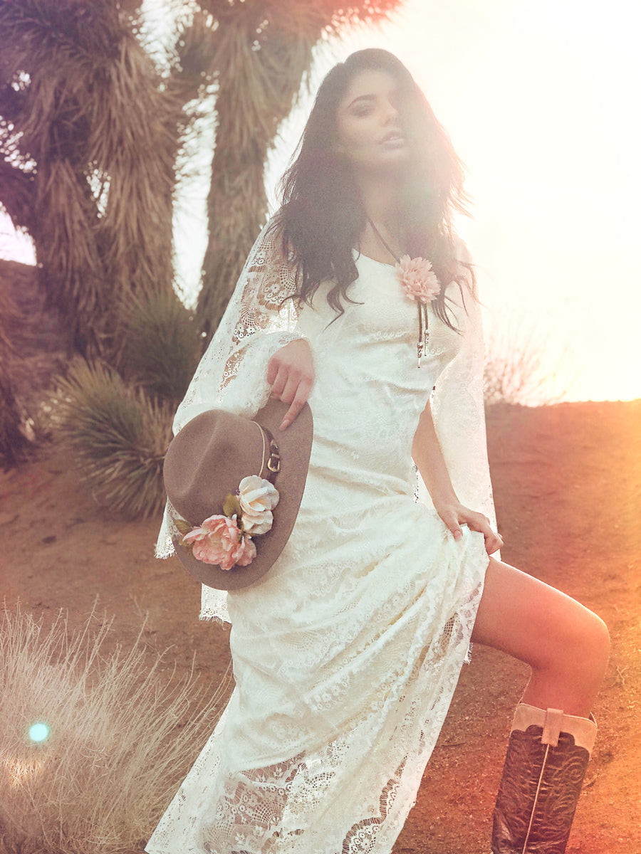 Festival and western inspired bohemian lace wedding dress with vintage feel and lace cape sleeves.