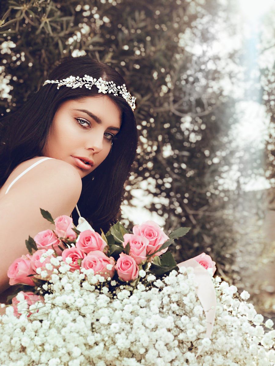 "A model wears the ""Verbena"" pearl and silver hair vine and wedding flower crown with crystal detailing"