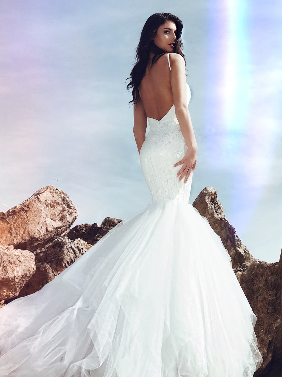 Backless mermaid wedding dress with tulle cathedral train and sparkle sequins on a lace sweetheart bodice.