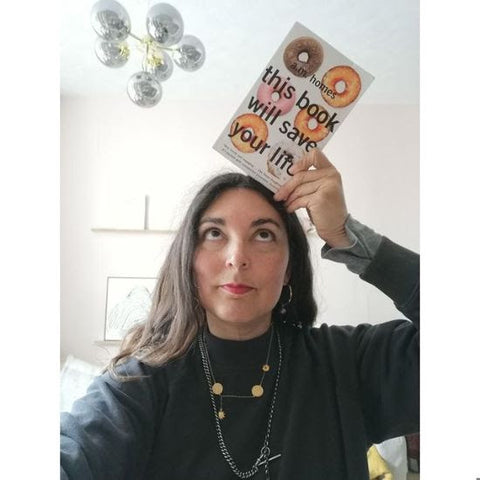 shop owner K holding a copy of This Book Will Save Your Life above her head