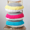 Stack of turquoise, pink and yellow 'Lola' crocheted cushions on a vintage chair