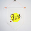Neon yellow 'SHINE' hand screen printed 100% cotton kids flag hung on dowel rod