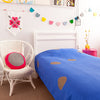 Gorgeous kids room with royal blue throw with gold spots on bed