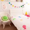 Gorgeous kids room with white throw with neon pineapples on bed