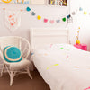 Gorgeous kids room with white throw with neon arrows on bed