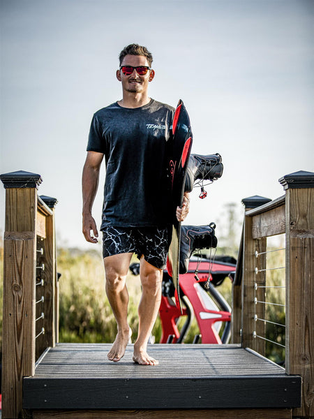 Nic Rapa walking on dock towards photographer with wakeboard under arm