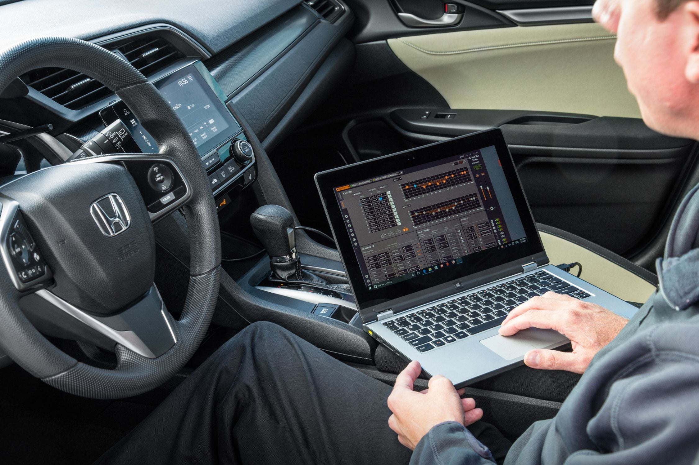 Hand on a Laptop Setting EQ with TüN Software in a Honda