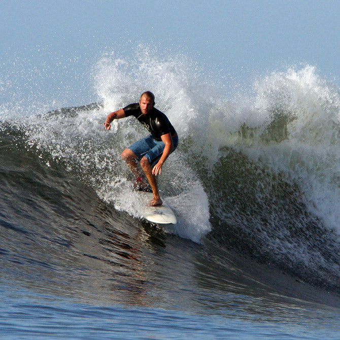 Mark is an avid surfer and is surfing a wave in the this image.  He loves the natural pain relief of rhelief®.