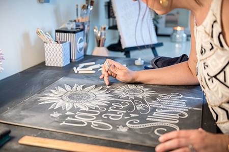 Valerie McKeehan of Lily & Val drawing a chalk image.