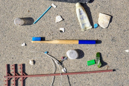 a mamap toothbrush among trash collected at the beach. mamap is a bamboo alternative to plastic toothbrush. it will biodegrade in 6 months compared to 1000 years for plastic brushes.