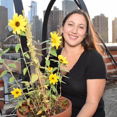 Suzan Hernandez pictured in Hell's Kitchen NYC with her rooftop grown sunflowers