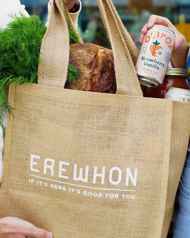 erewhon markets hemp reusable shopping bag with grocery items including mamap bamboo toothbrushes that give back