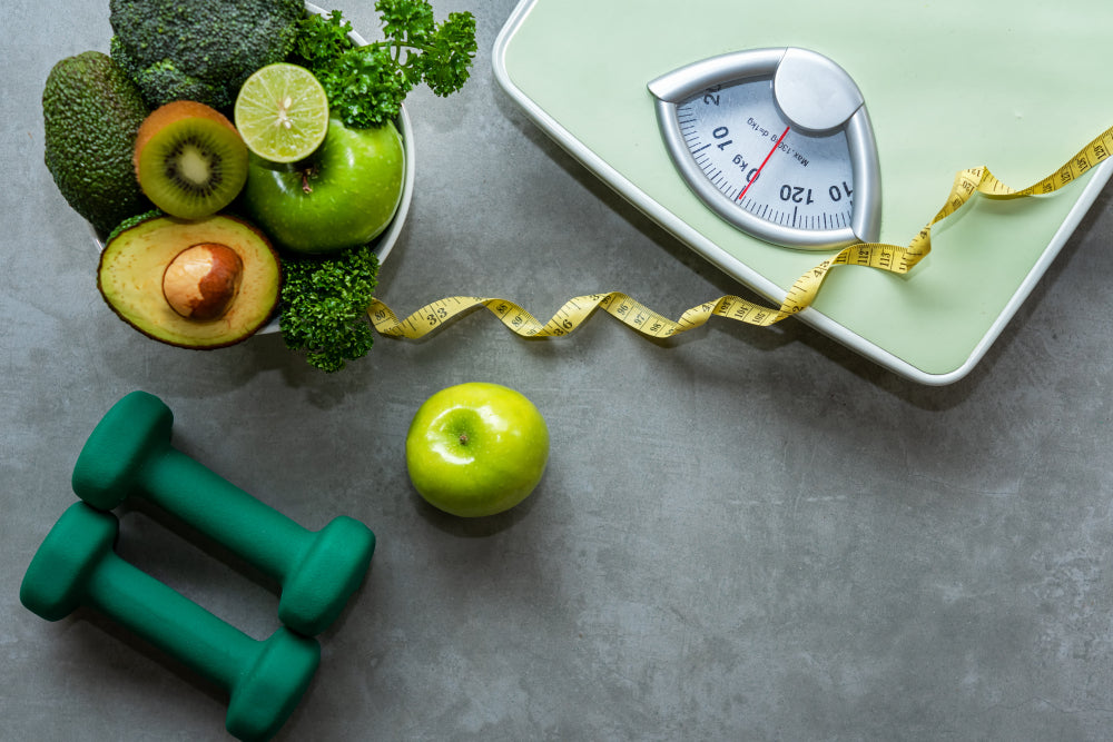Scale, weights and healthy food to promote weight loss with CBD.