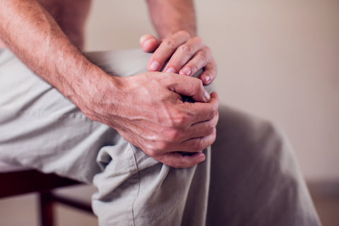 Man clutching knee because of arthritis pain.