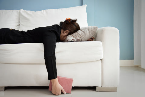 Woman laying on couch to relax after taking CBD for stress relief.
