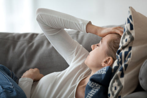 Woman lying on couch with hand to head because of chronic headache