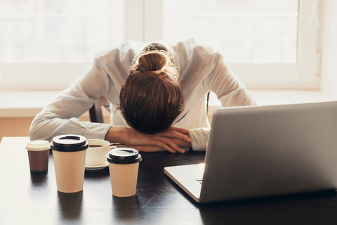 Woman at work stressed out and laying head on computer.