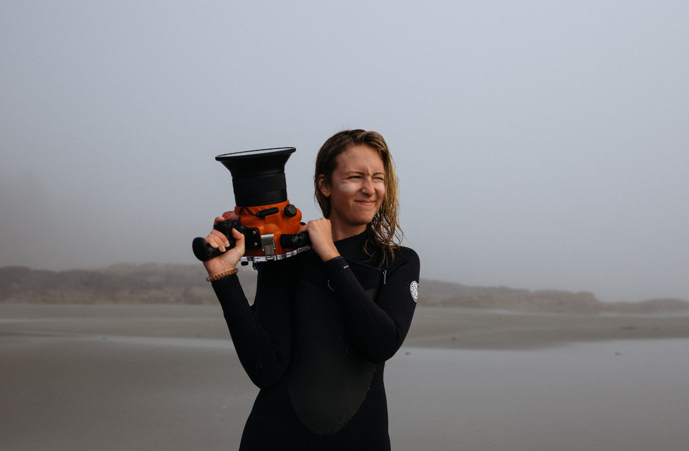 Johnie Gall in a wetsuit on the beach holding a camera