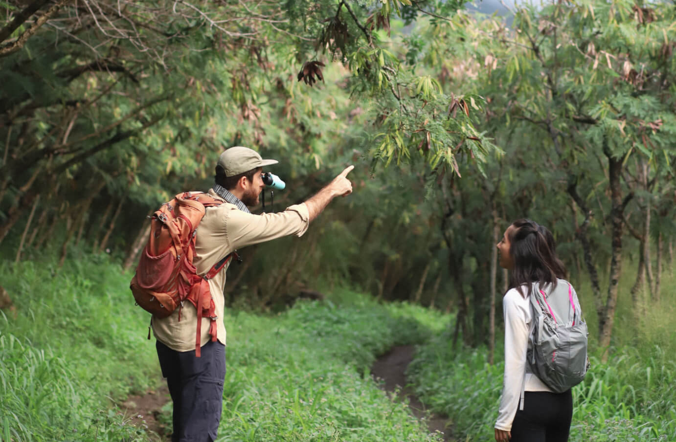 Peter Thoene pointing something out in a forest to a girl, while holding Nocs