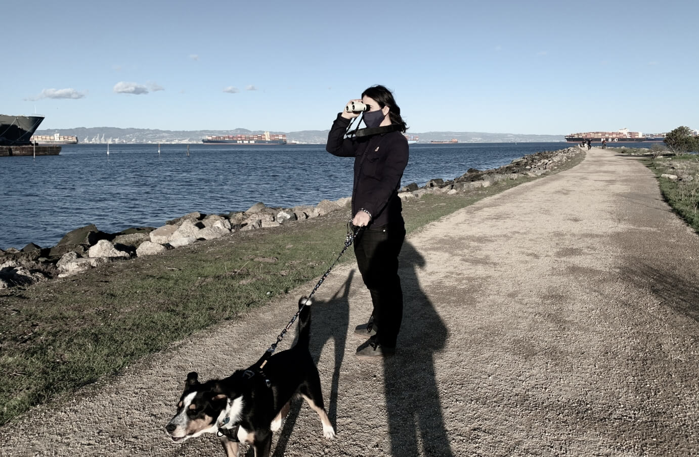 Picture of Lauren and her dog on a hike, holding Nocs and lookint through them across a body of water
