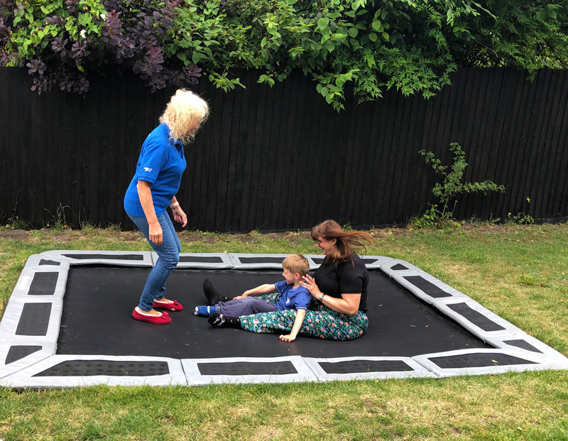 Child playing on in-ground trampoline