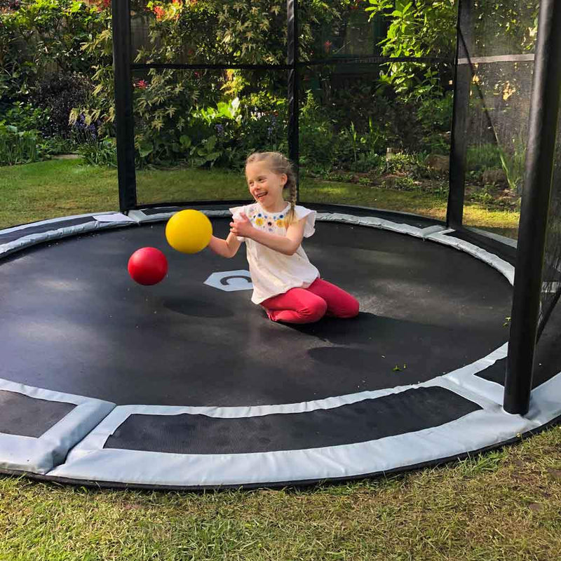 Child on 10ft in-ground trampoline with half net