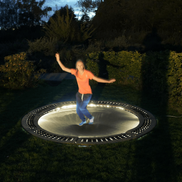 Child jumping on lit up trampoline