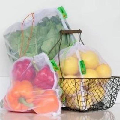 Red and orange bell peppers, big leafy lettuce, dozen of lemons in reusable produce bag