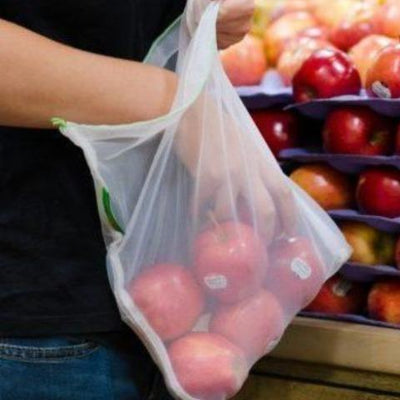 Man Placing red apples in reusable bag, shopping at the grocery store